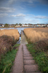 A small pier on the river Exe and the path to it. In the background the town Topsham. Devon. UK