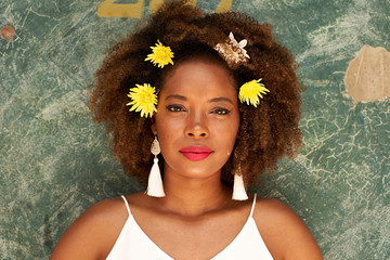 Portrait of young woman with red lips wearing earrings and flowers in her hair