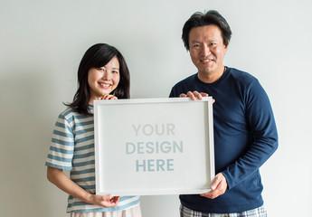 Couple Holding a Frame Mockup