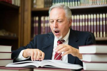 Sleepy business man lawyer yawning. Surrounded by many books