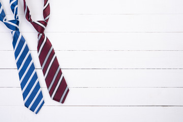 Happy fathers day concept. Top view of blue and red tie on white wooden table background. Flat lay.