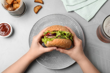 Woman holding tasty burger over plate at table, top view
