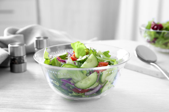 Bowl of tasty salad with cucumber and lettuce on table