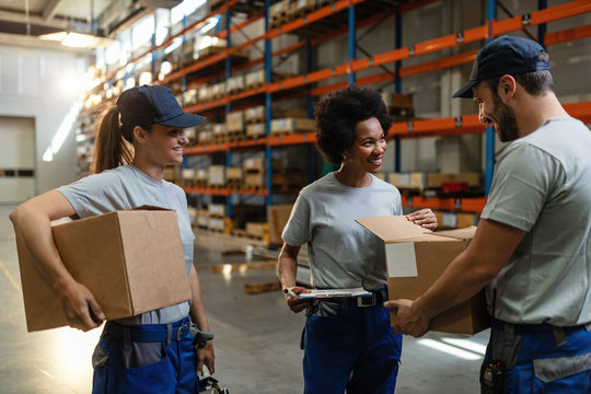Happy warehouse workers checking cardboard boxes before the shipment.