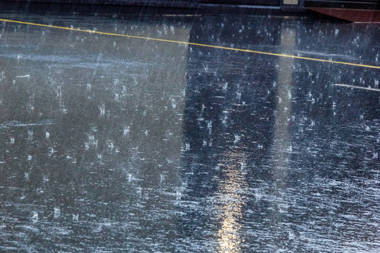 the pouring rain, with a thunderstorm and a thunder, water flows on asphalt forming pools, drops of a rain get to pools and splashes fly rereflecting light from the sun