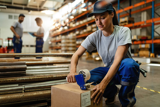Female worker using tape dispenser gun while packing boxes for the shipment.