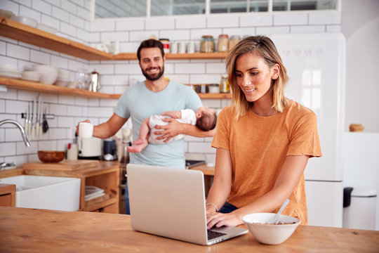 Multi-Tasking Father Holds Baby Son And Makes Hot Drink As Mother Uses Laptop And Eats Breakfast