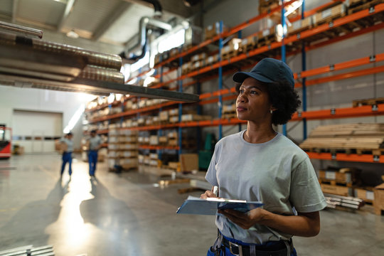 African American female worker taking notes while inspecting steel products in a warehouse.