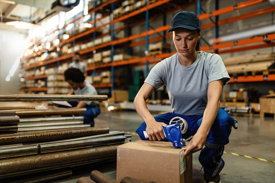 Female warehouse worker packing cardboard boxes for the shipment.
