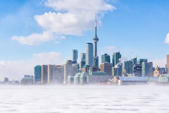 Toronto frozen lake Ontario. Early morning panoramic view of downtown with snow blizzard