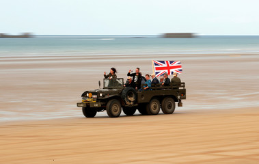 Enthusiasts enjoy a ride on a vintage army vehicle during a re-enactment of D-Day landings in Arromanches
