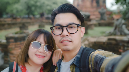 Traveler Asian couple using smartphone taking selfie while spending holiday trip at Ayutthaya, Thailand, Couple enjoy their journey at amazing landmark in traditional city.