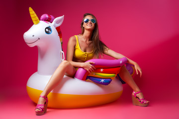 Concept summer mood, relaxation and beauty.Modern portrait of a young woman in a shorts, top and sandals resting on an inflatable unicorn mattress on an isolated pink background