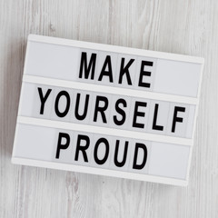 Light box with text 'Make yourself proud' on a white wooden background, top view. Flat lay, overhead, from above.