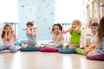 Kids seating on floor and show gestures making task in daycare