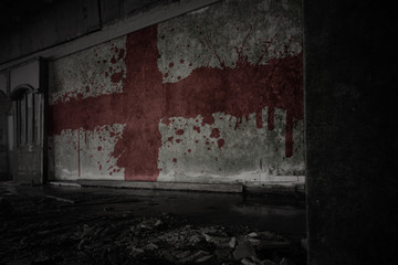 painted flag of england on the dirty old wall in an abandoned ruined house. Wall mural