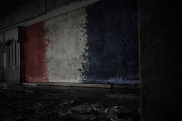 painted flag of france on the dirty old wall in an abandoned ruined house.