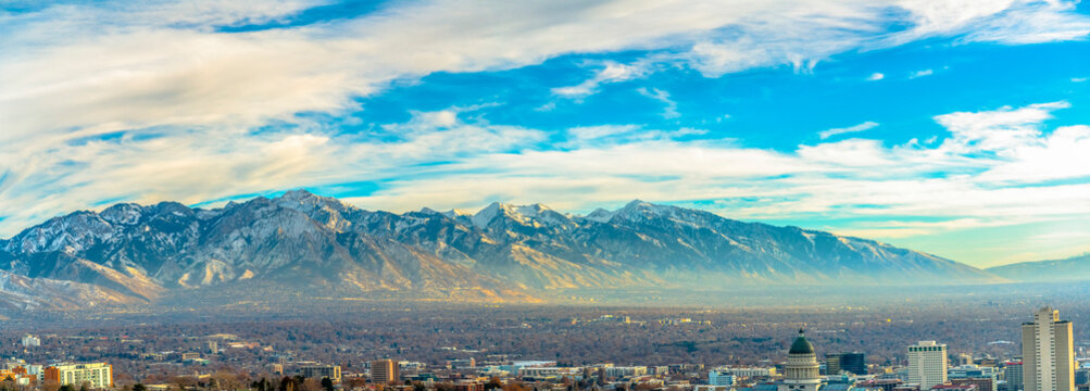 Panorama of downtown Salt Lake City against mountain and vibrant cloudy sky