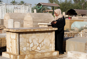 A woman reads the Koran at a cemetery during Eid al-Fitr, marking the end of the fasting month of Ramadan, in Baghdad