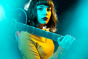 Beautiful young hipster woman with curly hair with red guitar in neon lights. Rock musician is playing electrical guitar. 90s style concept.