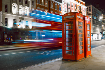 Light trails of a double decker bus next to the iconic telephone booth in London