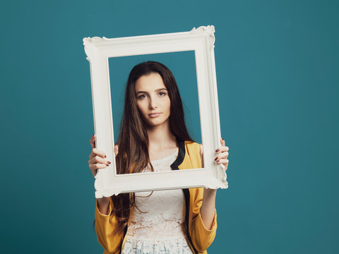 Beautiful woman posing and holding a frame