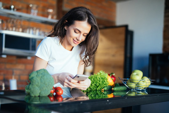 Portrait of her she nice-looking attractive lovely girl reading recipe online on the phone fresh lunch dinner farm organic vegs in the kitchen