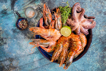 Top view of big plate with grilled shrimps and octopus tentacles decorated with greenery