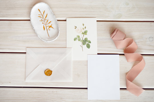 Feminine wedding desktop mock-up with blank paper card and Eucalyptus populus branch on white shabby table background. Empty space. Styled stock photo, web banner. Flat lay, top view