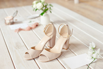 Wedding bouquet of white flowers, shoes and wedding rings on a wooden background