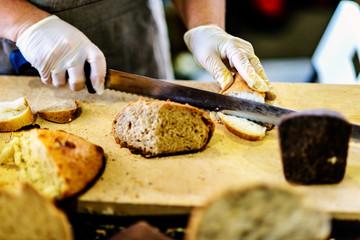 Woman cutting bread on wooden board. Bakehouse. Bread production.