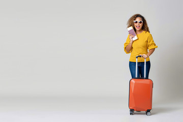 African American woman tourist with luggage holding passport and boarding pass