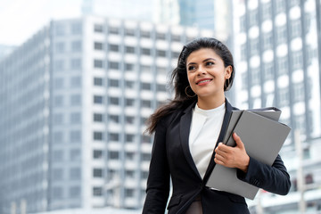 Young beautiful Latino businesswoman standing outdoors