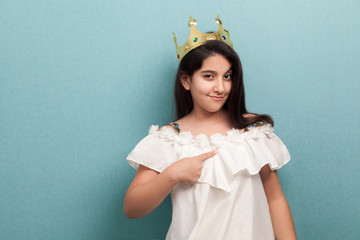 Young arrogance beautiful princess brunette girl wear in white dress and golden diadem crown, standing and pointing finger to herself, looking at camera. Indoor, isolated, studio shot, blue background