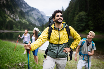 Group of happy friends with backpacks hiking together Wall mural