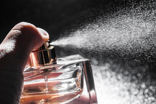 spraying perfume on dark background, closeup