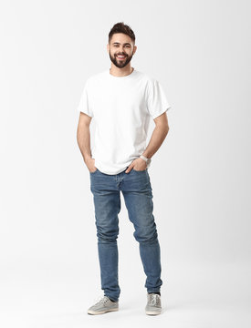 Stylish young man in jeans on white background