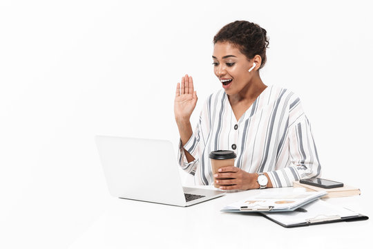African woman posing isolated over white wall background using laptop computer drinking coffee.