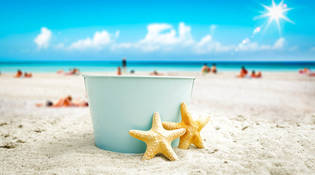 A blue metal bucket with free space for your product. The possibility of mounting bottles with drink, ice cream, food or other products. Blurry beach with people and ocean view.