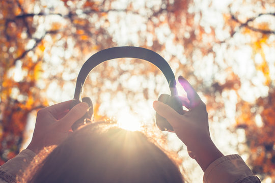 Female with headphones walking on the park listen sounds or music of autumn forest. Concept. Indian summer season
