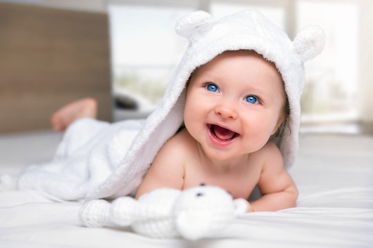 Happy six month old baby with a hooded towel lying on a bed and having fun