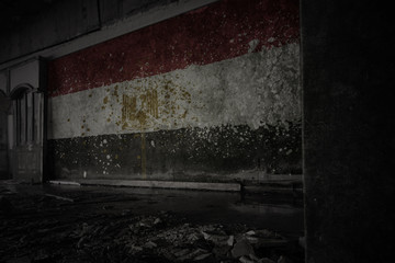 painted flag of egypt on the dirty old wall in an abandoned ruined house.