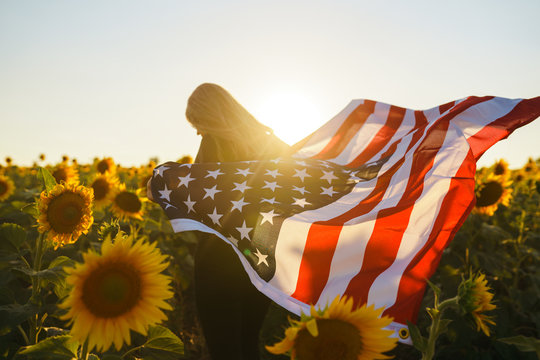 Beautiful girl with the American flag in a sunflower field. 4th of July. Fourth of July. Freedom. Sunset light The girl smiles. Beautiful sunset. Independence Day. Patriotic holiday.