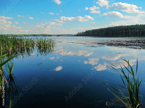 Wall mural Summer idyllic landscape with lake and sky. Bright day view with blue sky and white clouds and reflection in calm water surface. Lake Chebarkul, South Ural, Russia.
