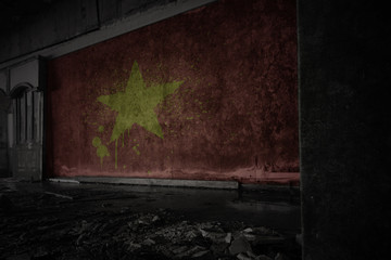 painted flag of vietnam on the dirty old wall in an abandoned ruined house.