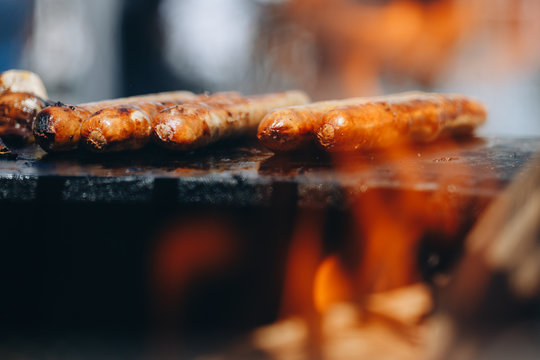 appetizing juicy chicken sausages on the grill close-up