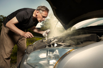 Obraz Aging man trying to fix broken car engine on lonely way - fototapety do salonu