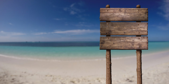 Wooden Board Sign at Sandy Beach at Tropical Island. Summer Vacation Concept