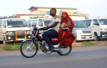 A Muslim woman carries her child as she rides on a motorbike taxi to attend the morning prayers of Eid al-Fitr, marking the end of the holy month of Ramadan, in Juba