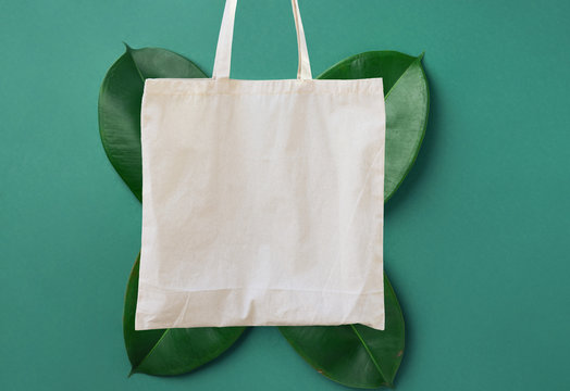 Blank white mockup linen cotton tote bag on green leaves foliage background. Zero waste reusable nature friendly materials. Environmental conservation recycling plastic free concept